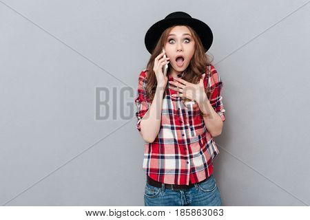 Portrait of a surprised shocked girl in plaid shirt talking on mobile phone and looking at camera isolated over gray background