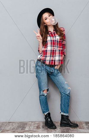 Full length portrait of a young cheerful girl in plaid shirt showing peace gesture and chewing bubble gum isolated over gray background