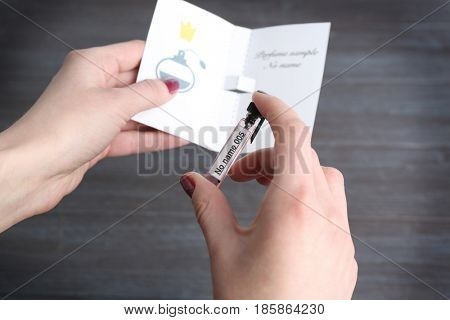 Female hand holding bottle with perfumes sample on blurred background