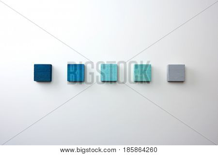 Index, menu or cover abstract back ground, consisting of five colored wooden blocks. On natural white background, with highlight on upper left. Blue, light blue to grey.