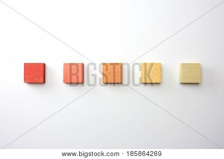 Index, menu or cover abstract back ground, consisting of five colored wooden blocks. On natural white background, with highlight on upper left. Orange to yellow.