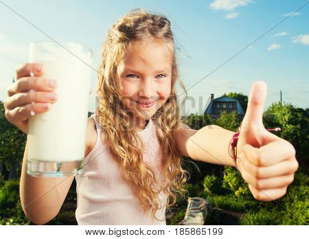 Girl holding glass with milk. Happy child at summer