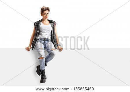 Punk girl sitting on a panel and looking at the camera isolated on white background