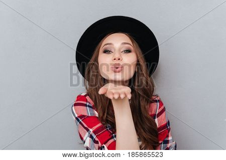 Portrait of a lovely pretty woman in hat and plaid shirt sending air kiss isolated over gray background