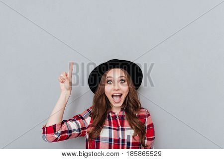 Portrait of a happy excited woman in hat and plaid shirt pointing finger up at copyspace and looking at camera isolated over gray background