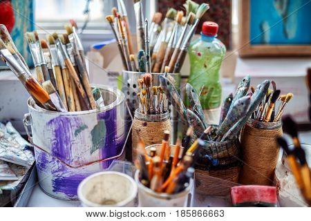 Artist workplace background. Art tools. Old dirty Paints background. Colorful artist palette. Soft toned. Creativity visual art concept. Art and craft. Closeup