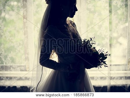 The bride holding bouquet in back lit