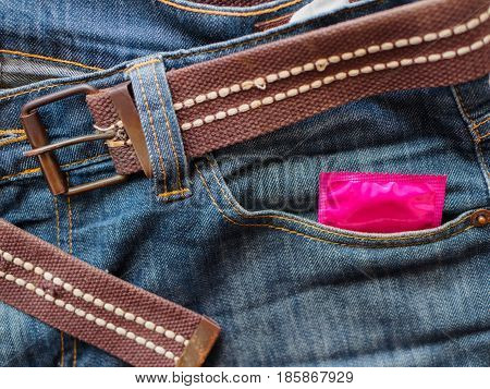 A pink Condom in the blue jeans pocket