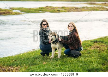 A girls is walking with a dog along the embankment. Beautiful Husky dog. The river. Spring.