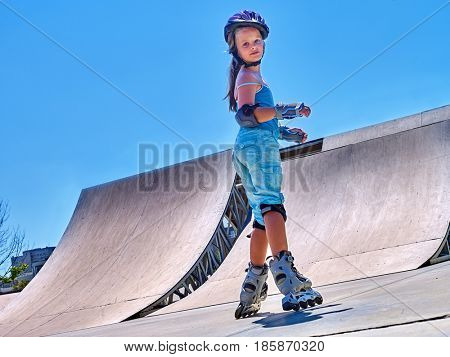 Girl roller in skates park. Child wear safety helmet do sport exercise. Active leisure outdoor kid in skatepark. Happy childhood in all seasons summer, spring, autumn. Competitions in skate park.