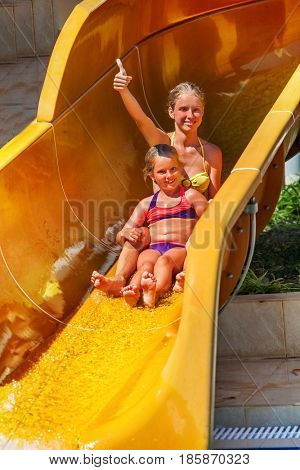 Swimming pool slides for children on water slide at aquapark . Summer kids ride holiday outdoor. Happy sisters girl in two-piece swimsuit with hands up in aqua park. Birthday in entertainment club.
