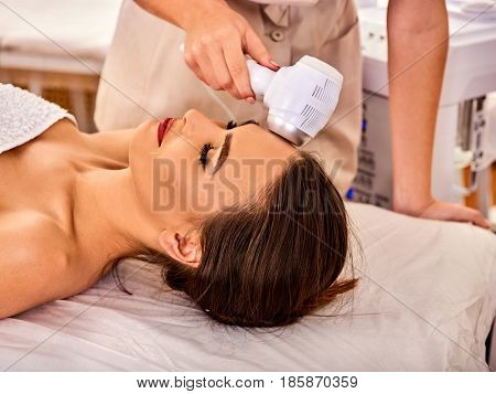 poster of Ultrasonic facial treatment on ultrasound face machine. Woman receiving electric lift massage at spa salon. Electronic stimulation female muscles microcurrent therapy . Technologies of rejuvenation.