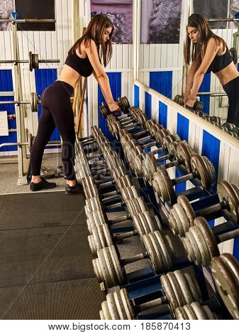 Woman holding dumbbell workout at gym. A lot of dumbbells in sport gym. Female hands lift dumbbells in sport gym. Fitness instructor girl chooses suitable bar for her client.