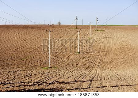 Electic poles and wires on ploughed land. Country side and urban landscape.