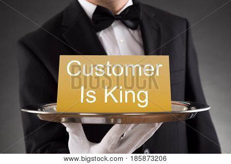 Close-up Of A Waiter Holding Tray With Text Customer Is King On Card