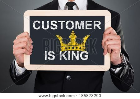 Close-up Of A Man Showing A Slate With Customer Is King Written On It