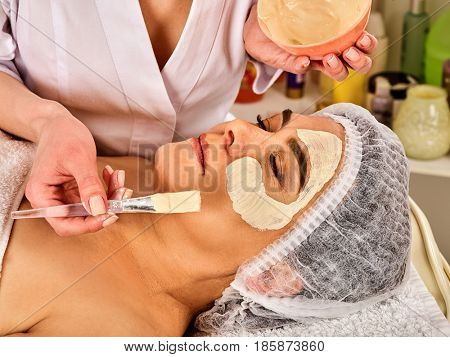 Collagen face mask . Facial skin treatment. Face of elderly elderly woman 50-60 years old receiving cosmetic procedure in beauty salon close up .