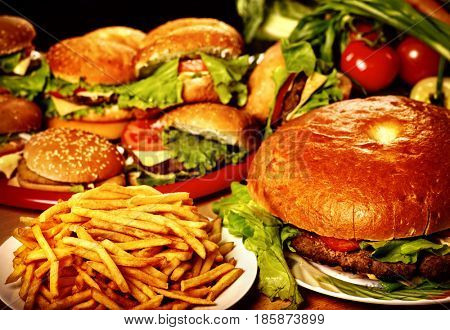 Fast food for large group friends. Unhealthy hamburger and french fries on plate for very hungry group people.