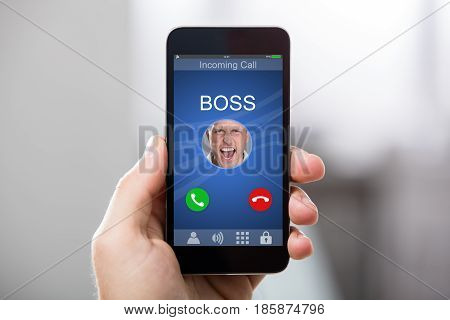 Close-up Of A Hand Holding Smart Phone With Boss's Incoming Call On Display