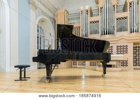 The grand piano in the concert hall of the late Baroque interior with the organ.