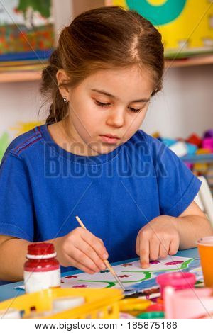 Small student girl painting in art school class. Child drawing by paints on table. Girl concentrates drawing. Craft drawing education develops creative abilities of children.