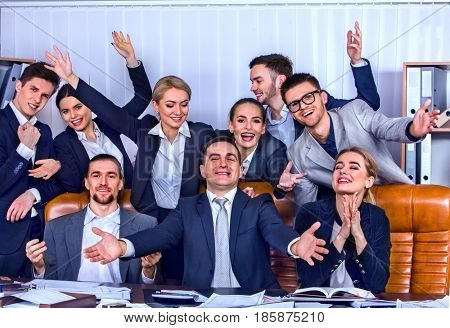 Business people office life of team people with hand up celebrate successful signing of contract. Cabinets with folders and jalousie background. Business team is happy from having won a business deal.