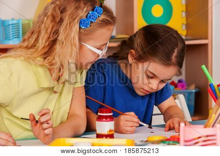 Small students girls painting in art school class. Children drawing by paints on table. Children are taught to draw. Craft drawing education develops creative abilities of kids.
