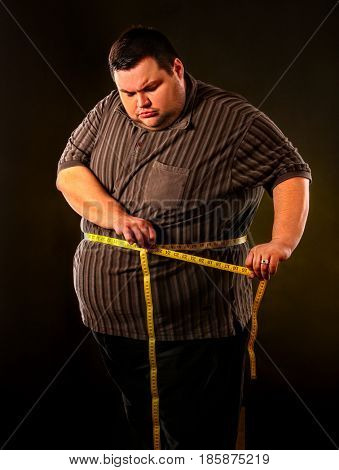 Man belly fat with tape measure weight loss around body on black background. First day of diet. Person is going to lose weight.