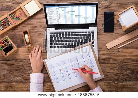 Businesswoman Marking A Date On Calendar At Workplace