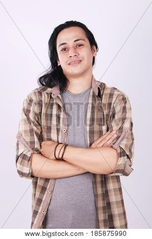 Photo image portrait of a cute young successful Asian male student with long hair smiling and standing with arms crossed in front of his chest