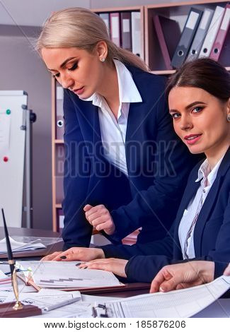 Business people office life of team people working with papers sitting table . Cabinets with folders background. Two young women in suits discuss an economic project.