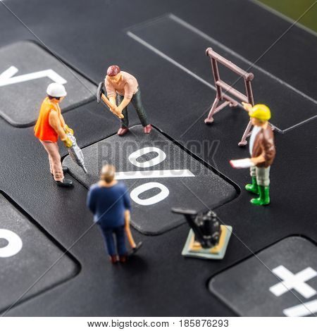 constatly changing interest rates / fixing the problem concept closeup of miniature figurine of workers reparing percentage button on a big black calculator