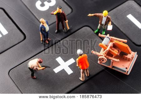 fixing the problem concept closeup of miniature figurine of workers reparing plus sign on a big black calculator