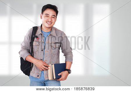 Photo image portrait of a cute young Asian male student standing looking at camera and smiling while holding some books