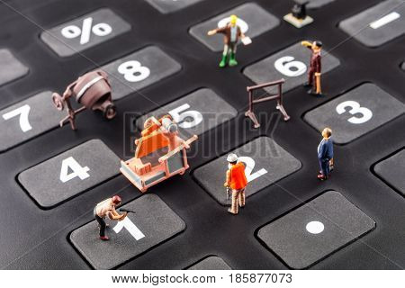fixing the problem concept closeup of miniature figurine of workers reparing number buttons on a big black calculator