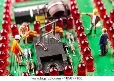 fixing the problem concept closeup of miniature figurine of workers reparing mainboard of electronic lights