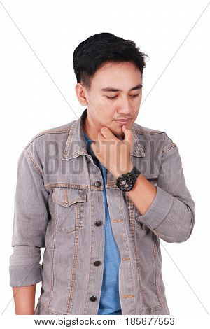 Photo image portrait of a cute young Asian male student standing looking down and thinking while touching his chin isolated on white