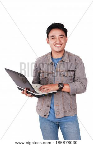 Photo image portrait of a cute young Asian male student standing and smiling while holding laptop and typing on it isolated on white