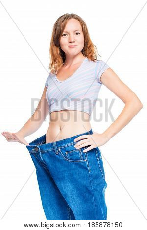 Slender Red-haired Girl Showing Old Pants After Losing Weight On White Background