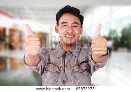 Photo image portrait of a cute young Asian man smiling and showing two thumbs up