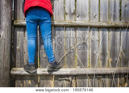 A teenage girl is standing over a fence