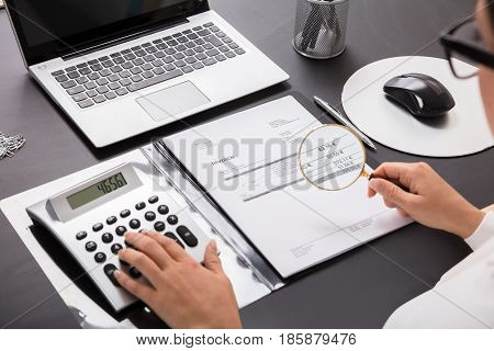 Close-up Of A Businesswoman Looking Invoice Through Magnifying Glass On Desk In Office