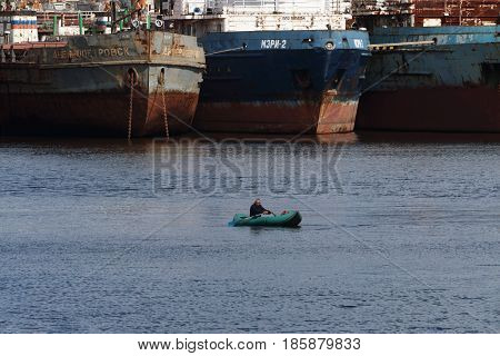 PERM RUSSIA - JUL 15 2016: Lonely fisherman on boat near big rusty cargo ships. In Perm there is Shipyard Kama serving large cargo and passenger ships