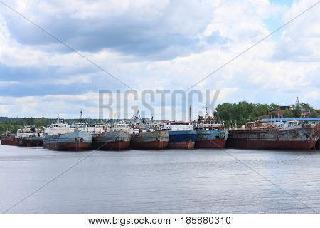River with many rusty cargo ships and sky with clouds on summer day