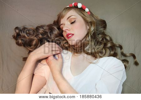 Cute woman in roses wreath and white dress with curly hair lies on bed