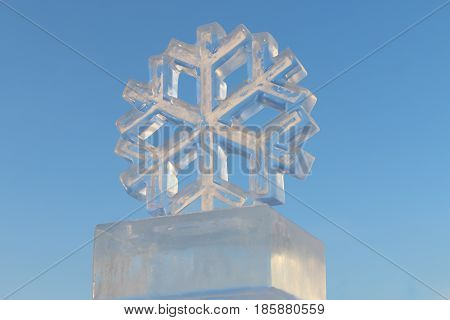 Big man-made ice snowflake and pure blue sky at sunny winter day