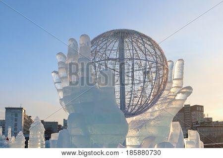 PERM RUSSIA - JAN 18 2017: Globe in hands art object Ice town of Perm in 2017 Ekosad - largest in Russia