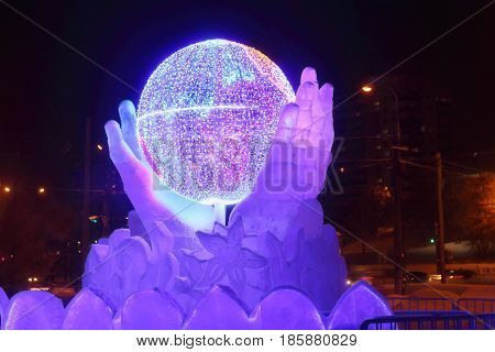 PERM RUSSIA - JAN 10 2017: Globe in hands with illumination at evening Ice town of Perm in 2017 Ekosad - largest in Russia