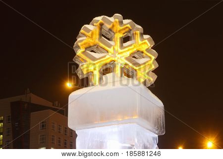 PERM RUSSIA - FEB 1 2017: Snowflake with yellow illumination at night Ice town of Perm in 2017 Ekosad - largest in Russia