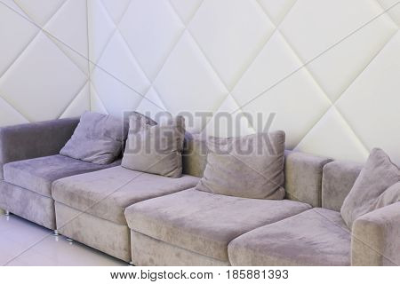 Big grey couch with pillows is in white empty room for resting